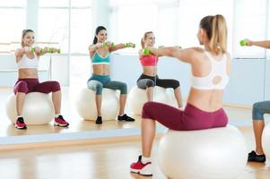 Mujeres haciendo ejercicio con pesas.