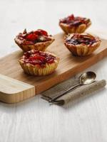 Tarts with apples on a cutting board