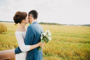 groom kissing bride in field
