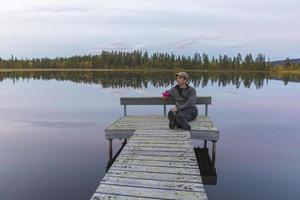 hombre sentado en el embarcadero en el lago