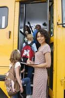 Profesor parado en autobús mientras los estudiantes abordan