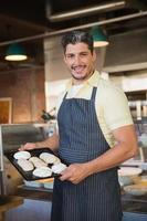 Smiling worker in apron holding tray of meringue