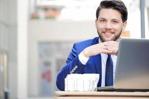 agradable joven sentado en la cafetería foto