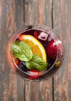 Orange and apple sangria on a wooden background