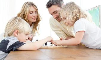 familia jugando al ajedrez en una mesa foto