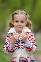 Retrato de una niña con dientes de León en manos foto