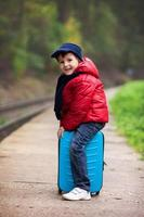 Adorable cute little child, boy, waiting on a railway station photo