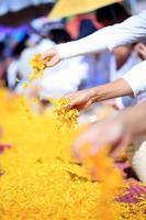 mucha gente esparce flores en el camino para caminar monje. foto