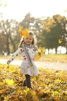Happy Kid Throwing Leaves Outdoor In Park photo