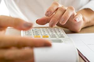 mujer banquera calculando gastos e ingresos usando la suma de machi