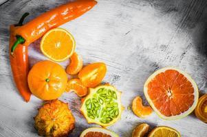 Naranja frutas y verduras sobre fondo rústico
