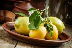 limones frescos con hojas en un plato de arcilla foto