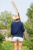 rubia jardinería sosteniendo un rastrillo
