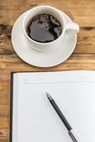 cuaderno con pluma y taza de café sobre fondo de madera.