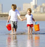 Siblings hold hands on the beach