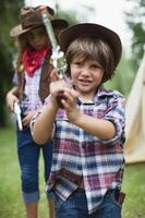 Boy in cowboy hat with toy pistol
