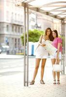 twee jonge tienermeisjes wachten bij de bushalte.