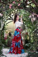 atractiva mujer de pie en una larga falda roja en jardín de flores