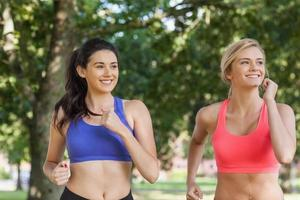 Two sporty women jogging in a park photo