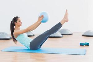 mujer joven deportiva estirando el cuerpo en el gimnasio foto