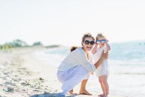 Porträt der glücklichen Mutter und des Babys in der Sonnenbrille am Strand