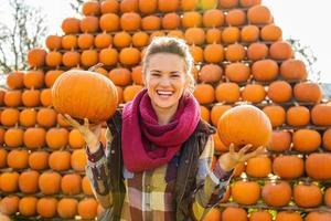portret van lachende vrouw met pompoenen in de herfst buiten