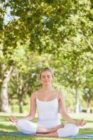 mujer tranquila sentada meditando sobre una estera del ejercicio foto