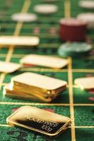 Gambling chips and gold bars on roulette table photo