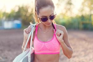 Attractive fit woman in sportswear training outdoors, female athlete with photo