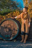 Portrait of young woman near wooden barrel in autumn outdoors