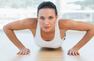 Determined beautiful woman doing push ups in gym