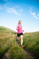 hermosa joven corre a campo traviesa en una montaña foto