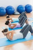 Determined women doing sit ups at fitness studio