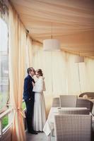 bruiloft. pasgetrouwden zitten in een gezellig café beige landschap