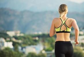 Young woman running outdoors. Back view. photo