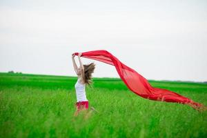 Young lady runing with tissue in green field. Woman and