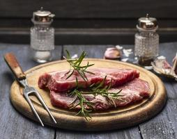 raw meat with rosemary, garlic, salt pepper  wooden board  fork