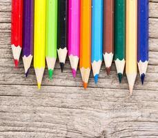 Lápices de colores sobre fondo de madera.
