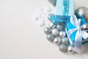 silver Christmas balls and gifts on wooden table