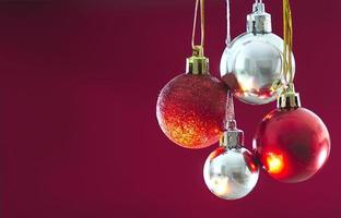Red and silver Baubles hanging against solid Background