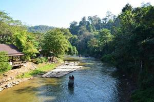 Selva tropical y turista montando en elefante en el río