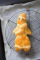 Homemade traditional german man-shaped bread on cooling rack photo