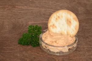 dish of salmon pate with parsley on wood photo