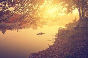 Vintage photo of idyllic landscape with foggy lake in sunrise