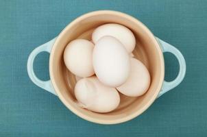 Duck eggs in blue ceramic pot photo