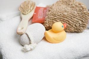 bienestar, toalla blanca con piedra pómez, cepillo para el pelo, pato de goma