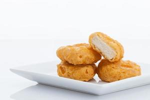 Group of fried chicken nuggets i on white dish photo
