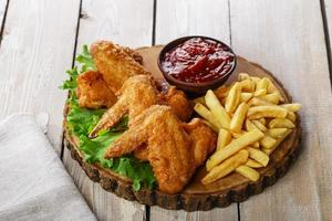 Fried chicken wings with sauce and French fries photo