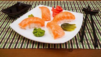 sushi syake en plato cuadrado blanco con palos negros foto