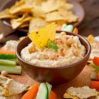Healthy homemade hummus with vegetables, olive oil and pita chips